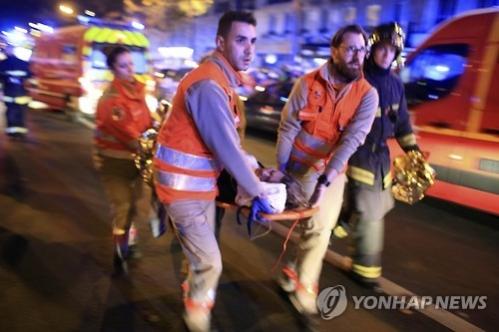 ▲한 여성이 13일(현지시간) 파리 바타클란 극장에서 발생한 테러로 부상해 구조대원들에 의해 실려가고 있다. AP/연합뉴스