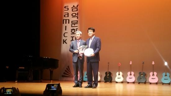 ▲삼익악기 김종섭 회장(오른쪽)이 22일 기타 기증식을 갖고, 곽상욱 오산시장과 기념촬영을 하고 있다.(사진=삼익악기)