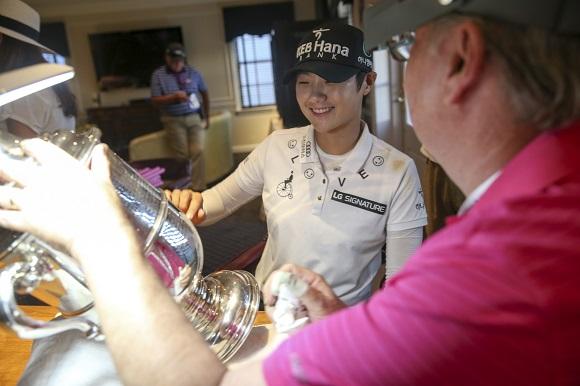 ▲US여자오픈 챔피언십 우승트로피에 자신의 이름이 새겨지는 것을 바라보며 미소짓는 박성현. 사진=USGA