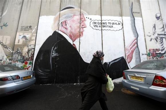 ▲이스라엘 베들레험 웨스트뱅크 시의 한 건물 담벼락에 도널드 트럼프 미국 대통령이 유대인 전통모인 키파를 쓰고 기도하는 모습이 그려져 있다. 베들레헴/EPA연합뉴스