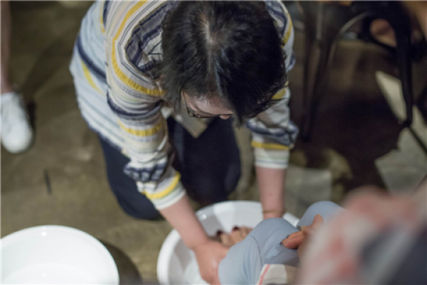 ▲한양사이버대학교 사회복지학부 구혜영 교수가 학생의 발을 씻겨 주고 있다.(사진제공=한양사이버대)