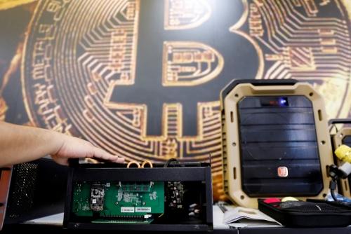 ▲비트코인 동전 이미지 앞에 가상화폐 채굴용 컴퓨터가 놓여져 있다. 로이터연합뉴스