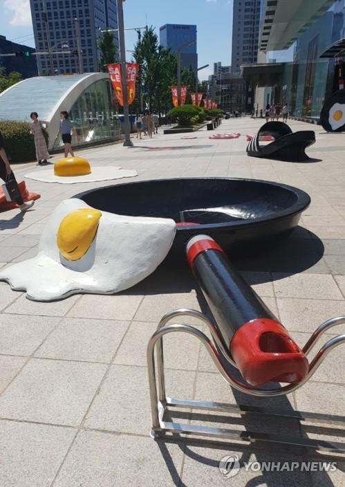 ▲15일 오후 현대백화점 대구점 앞에서 시민들이 더위에 익은 달걀프라이와 녹아내린 슬리퍼 조형물 사이를 지나가고 있다.(연합뉴스)