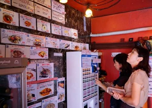 ▲일본 도쿄의 한 프렌치 레스토랑에서 고객이 벽에 붙은 사진을 보며 기계로 메뉴를 주문하고 있다. 출처 니혼게이자이신문