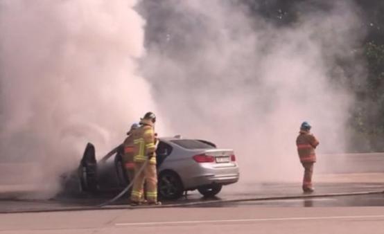 ▲9일 오전 8시 50분께 제2경인고속도로 안양방면을 향해 달리던 BMW 320d에 화재가 발생, 소방대원들이 이를 진화하고 있다. (연합뉴스)