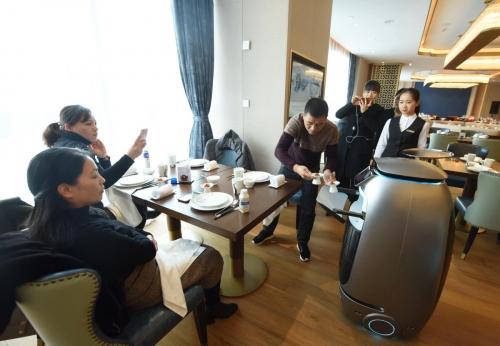 ▲중국 최대 전자상거래업체 알리바바가 18일(현지시간) 저장성 항저우에 개장한 미래형 호텔 '페이주부커(菲住布渴)호텔'에서 로봇이 고객에게 음식을 전달하고 있다. 항저우/신화연합뉴스