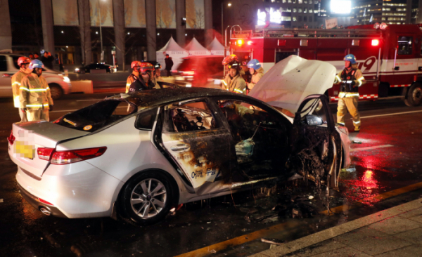 ▲9일 오후 6시께 서울 광화문 인근에서 택시기사의 분신 시도로 추정되는 택시 화재가 발생, 소방관들이 화재를 진화하고 있다. (연합뉴스)