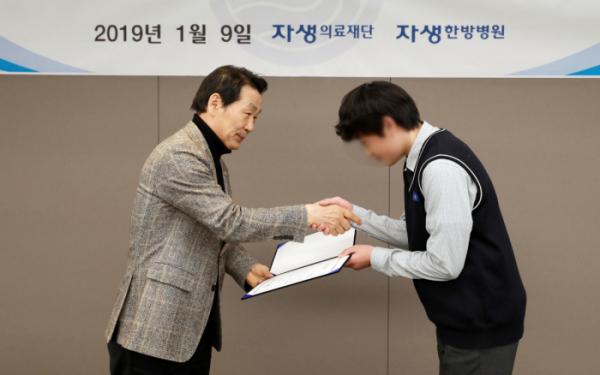 ▲자생의료재단 박병모(왼쪽) 이사장이 장학생에게 장학증서를 전달하고 있다.