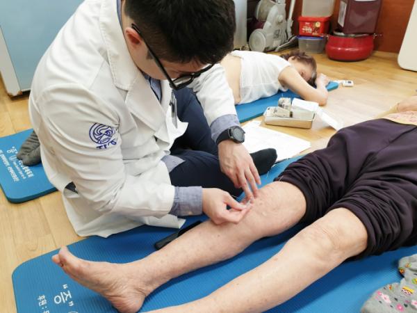 ▲자생한방병원 의료진이 복지관을 방문한 환자에게 침 치료를 실시하고 있다.(자생한방병원 제공)