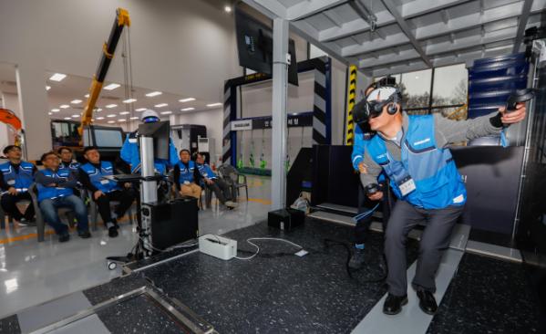 ▲대림 임원이 VR 장비를 착용하고 고소작업을 체험하고 있다(사진=대림산업)