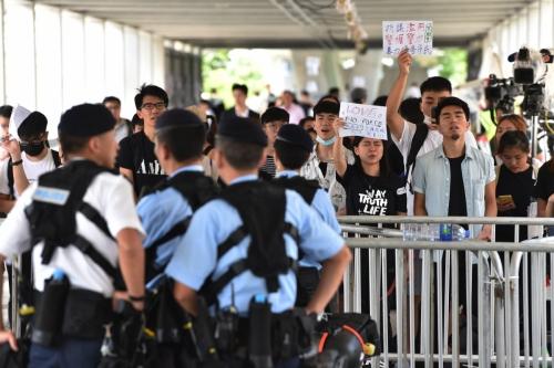▲홍콩 정부청사 인근에서 14일(현지시간) 시민이 시위하는 가운데 경찰들이 경비를 서고 있다. 홍콩/AFP연합뉴스