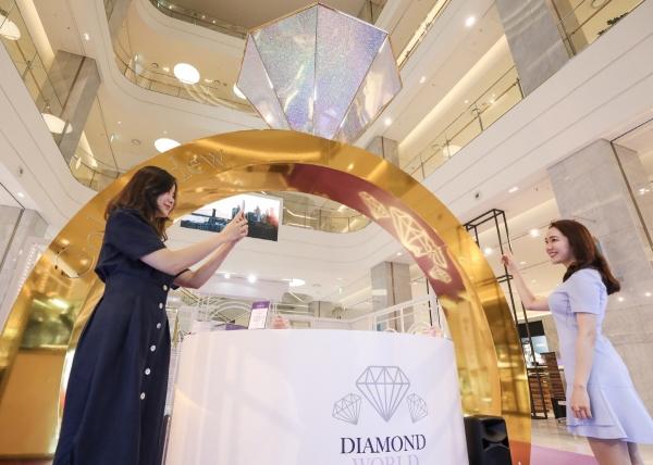 ▲25일 오전 현대백화점 판교점 1층 열린광장에서 고객들이 4M 높이의 다이아몬드 반지 모형이 설치된 '골든듀 다이아몬드 월드' 팝업스토어를 구경하고 있다.