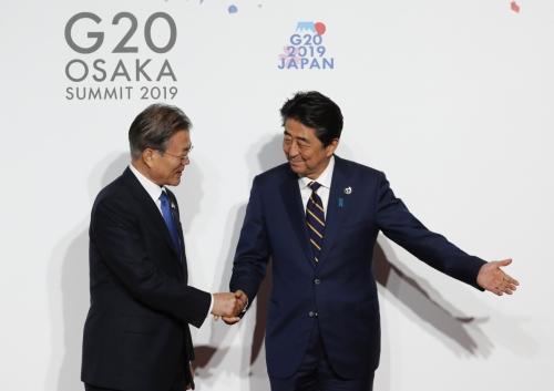 ▲아베 신조(오른쪽) 일본 총리가 지난달 28일(현지시간) 오사카에서 주요 20개국(G20) 정상회의 단체 기념사진을 찍고자 행사장에 도착한 문재인 대통령과 악수하고 있다. 오사카/AP뉴시스