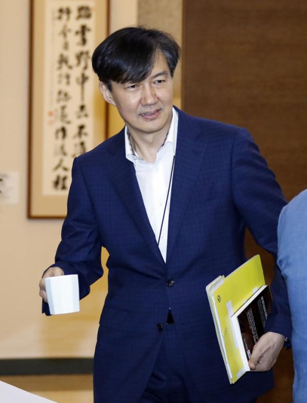 ▲청와대 조국 민정수석이 22일 오후 청와대에서 열린 수석·보좌관회의에서 '일본회의의 정체'라는 책을 들고 입장하고 있다.(연합뉴스)