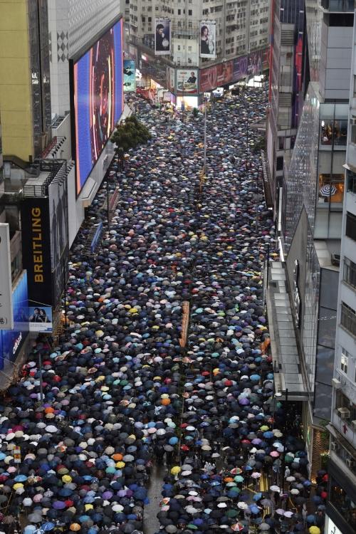 ▲18일(현지시간) 송환법 반대 집회에 참가한 홍콩 시민이 우산을 쓰고 도심을 행진하고 있다. 홍콩/AP연합뉴스