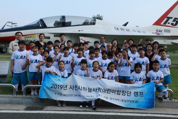 ▲지난 7월 KAI가 후원하고 있는 하늘사랑 어린이합창단원들이 다양한 항공체험을 한 뒤 T-50 고등훈련기를 배경으로 기념촬영을 하고 있다. KAI 하늘사랑아동합창단은 2017년 3월 창단됐다. 사진제공 KAI