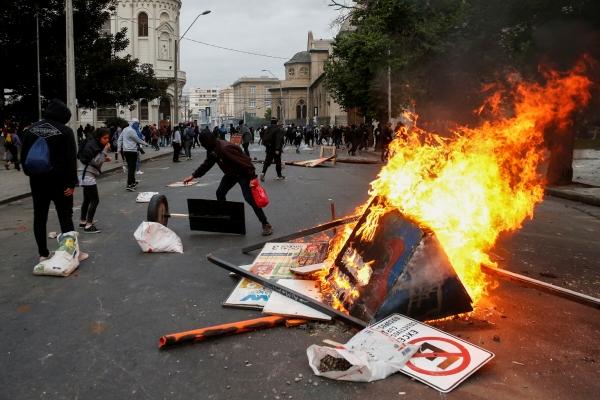 ▲19일(현지시간) 칠레 산티아고에서 정부에 항의하는 시위대가 불을 지르고 있다. 산티아고/로이터 연합뉴스.