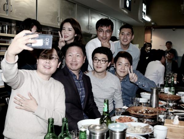 ▲최태원 SK그룹 회장이 28일 서울 광화문 인근의 한 대중음식점에서 저녁식사를 겸한 번개 행복토크를 열고 구성원들과 함께 사진을 찍고 있다. (사진제공=SK그룹)