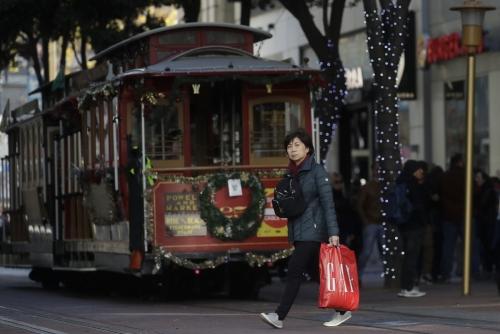 ▲미국 샌프란시스코에서 블랙프라이데이 당일인 29일(현지시간) 한 여성이 쇼핑백을 들고 도로를 건너가고 있다. 샌프란시스코/AP뉴시스