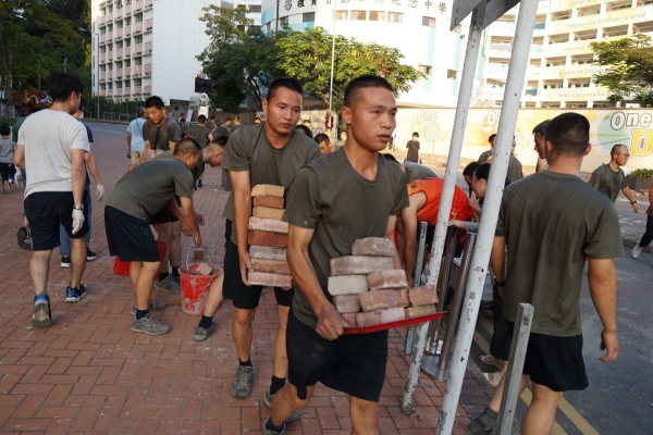 ▲홍콩에 주둔하는 중국 인민해방군 군인들이 16일(현지시간) 막사 인근의 도로에 설치된 벽돌들을 치우는 등 청소작업을 하고 있다. 홍콩/AFP연합뉴스