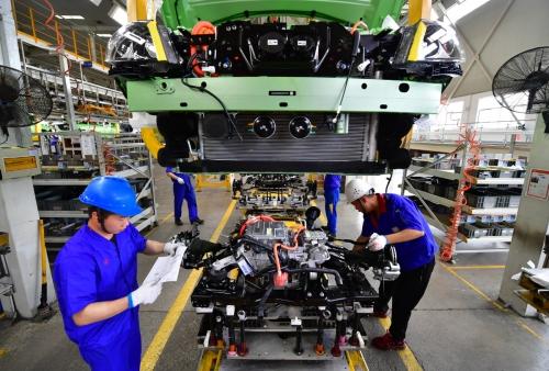 ▲중국 시안의 BYD 공장에서 근로자들이 전기차 차체에 모터를 장착하고 있다. 시안/신화뉴시스