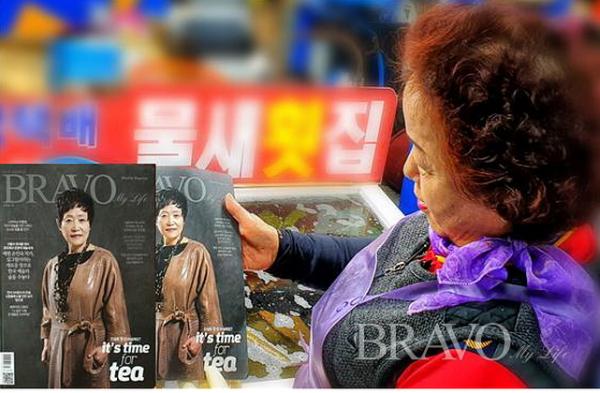▲수산시장 물새횟집 주인이 브라보마이라이프를 받아 보고 있다(변용도 동년기자)