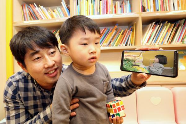 ▲LG유플러스는 어린이들이 선호하는 동화, 자연관찰, 과학 등의 콘텐츠를 3D AR로 생동감있게 즐길 수 있는 모바일 교육 애플리케이션 'U+아이들생생도서관'을 17일 출시한다고 14일 밝혔다. 자녀와 부모고객이 U+아이들생생도서관을 이용하고 있는 모습. (LG유플러스 제공)