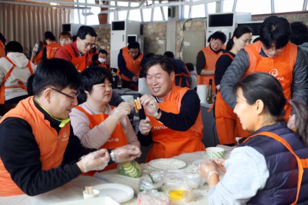 ▲'2020 신임 임원 봉사활동'에 참여한 한화그룹 신임 임원들이 발달장애인들과 함께 설 명절 음식을 만들고 있다. (사진제공=한화그룹)