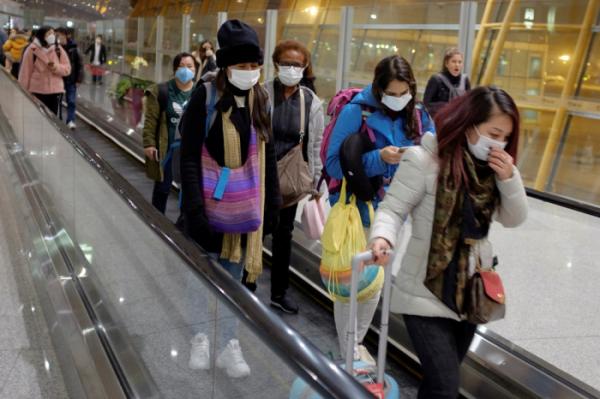 ▲25일 중국 베이징 공항에 도착한 여행객들이 마스크를 쓴 채 에스컬레이터를 타고 이동하고 있다. (연합뉴스)