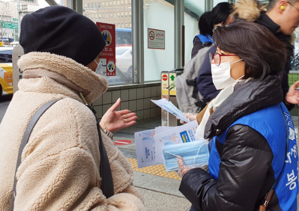 ▲강남자생봉사단원이 시민에게 마스크를 전달하고 신종 코로나바이러스 감염증 예방법을 설명하고 있다.(자생한방병원)