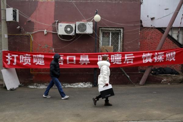 ▲중국 베이징의 한 골목에서 13일(현지시간) 행인들이 마스크를 쓰고 '기침을 할 때 코와 입을 가리고 기침 후에는 눈을 만지지 마시오'라고 적힌 현수막 앞을 걸어가고 있다. 베이징/EPA연합뉴스