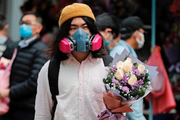 ▲홍콩에서 밸런타인데이인 14일(현지시간) 한 남성이 방독면을 쓰고 꽃다발을 든 채 서 있다. 홍콩/로이터연합뉴스