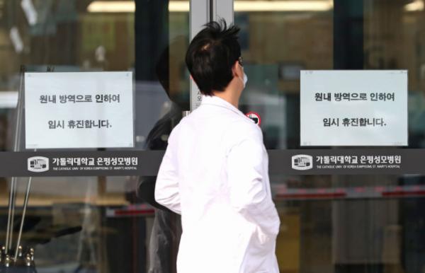 ▲21일 오전 환자이송요원 중 1명이 신종코로나바이러스 감염증(코로나19) 1차 양성 판정을 받은 서울 은평성모병원에 임시 휴진 안내문이 붙어 있다.  (연합뉴스)