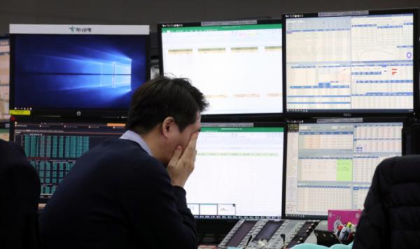 ▲ 13일 서울 을지로 하나은행 본점 딜링룸에서 한 외환딜러가 생각에 잠겨 있다. (연합뉴스)