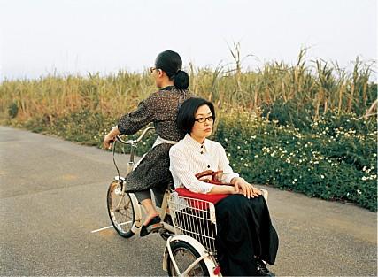▲캐리어를 포기하고  사쿠라의 자전거에  탄 타에코.   (영화 '안경' 캡춰 )