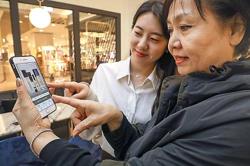 ▲한 소비자가 모바일 앱을 이용해 쇼핑하고 있다.(현대백화점)