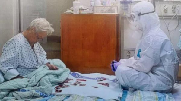 ▲음압병동에 홀로 격리된 할머니와 함께 방호복을 입은 채 화투 놀이를 하는 간호사의 사진이 인터넷에서 화제가 되고 있다. (대한간호협회)