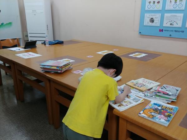 ▲서울시교육청 개포도서관은 코로나19발생 후 어린이실 의자를 없앴다. 앉아서 책을 볼 수 없어 서서 책을 보고 있는 어린이 모습.(박응서)