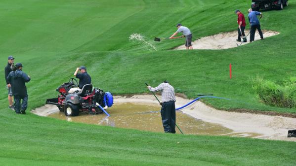 ▲순식간에 내린 폭우에 조직위가 물을 퍼내고 있다.(사진=LPGA)