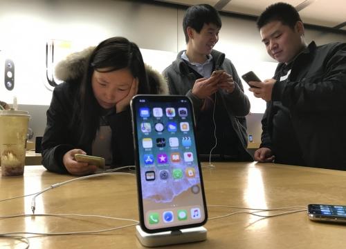 ▲지난해 11월 중국 베이징 애플스토어에서 소비자들이 아이폰X를 살펴보고 있다. 베이징/AP뉴시스