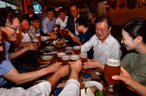 ▲문재인 대통령이 26일 오후 서울 광화문 인근 한 호프집에서 퇴근길 시민들과 만나 건배하고 있다.(연합뉴스)