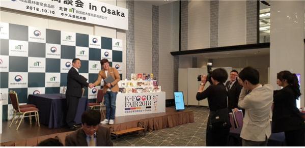 ▲2018년 10월 10일 오사카에서 열린 한국농수산식품유통공사 주관 K-Food Fair에서 아임디엔엘 정경조 대표(단상 우측)와 일본 YURI 이광석 대표가 아임떡볶이 일본 수출을 위한 협약을 맺었다.(사진제공=아임디엔엘)