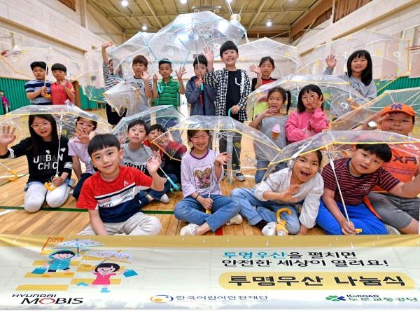 ▲서울 고산초 어린이들이 현대모비스의 투명우산을 들고 포즈를 취하고 있다. 현대모비스의 투명우산은 올해로 100만 개 나눔을 돌파한다. 사진제공 현대모비스
