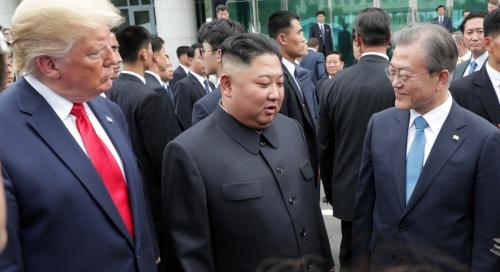 ▲문재인(오른쪽) 대통령이 6월 30일 판문점 자유의 집 앞에서 김정은 북한 국무위원장, 도널드 트럼프 미국 대통령과 이야기를 나누고 있다. 뉴시스