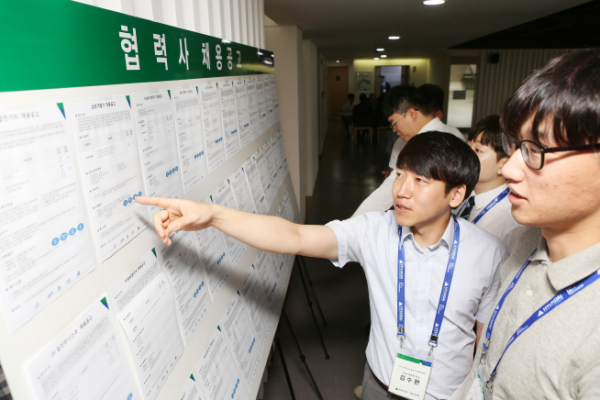 ▲채용박람회를 찾은 기술교육원 졸업생이 채용공고를 보고 있다(사진=현대건설)