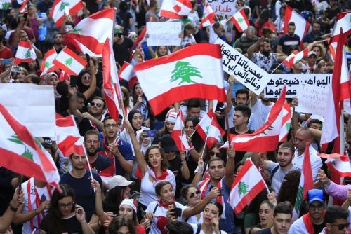 ▲레바논 베이루트에서 21일(현지시간) 시민이 국기를 흔들면서 반정부 시위를 벌이고 있다. 베이루트/로이터연합뉴스
