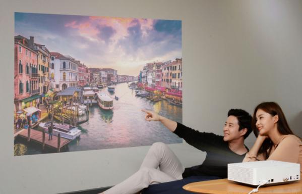 ▲서울 여의도 LG트윈타워에서 모델들이 'LG 시네빔 4K' 프로젝터가 구현하는 초대형 화면으로 영상을 즐기고 있다.(사진제공=LG전자)