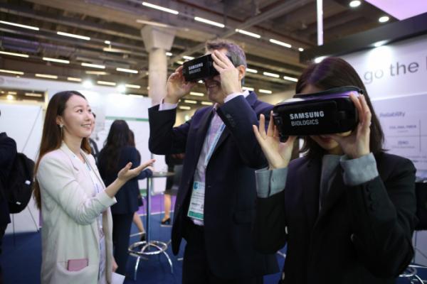 ▲5~7일(현지시간) 독일 프랑크푸르트에서 열리는 'CPhI 월드와이드 2019'의 삼성바이오로직스 부스 방문객들이 VR 체험을 하고 있다. (사진제공=삼성바이오로직스)