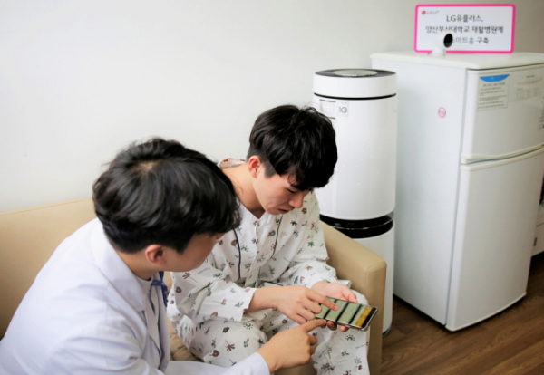 ▲U+스마트홈 서비스가 구축된 양산부산대학교병원 재활병동의 트랜짓하우스에서 U+스마트홈 스피커와 홈IoT를 체험하는 모습.  (사진제공=LG유플러스)