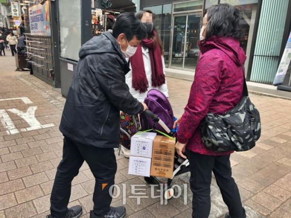 ▲28일 서울 중구 명동에서 한 중국인 관광객 가족이 구입한 마스크 상자를 유모차에 싣고 있다.  (홍인석 기자 mystic@)